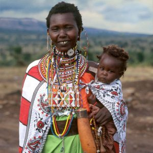 A Maasai woman wearing multi-colored, beaded jewelry holds a child on her hip.
