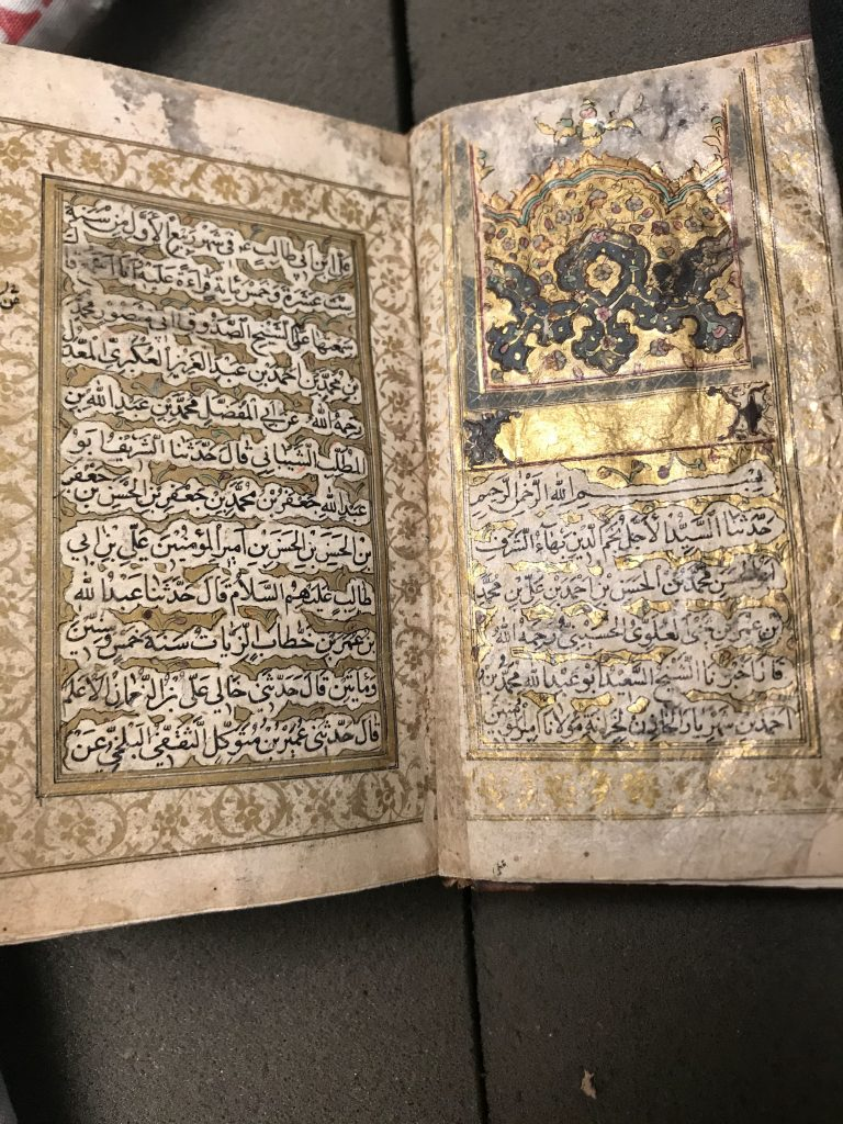 An open two page spread of an Arabic manuscript with gold leaf decorations