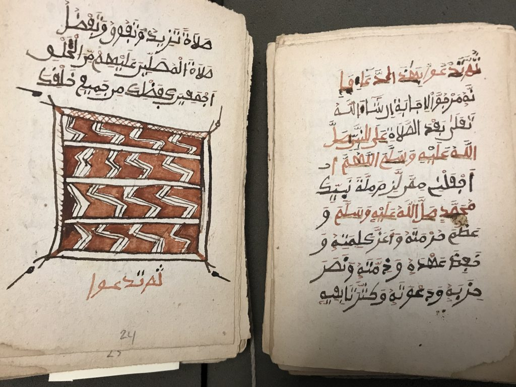 An open page of an Arabic manuscript with a drawing and red and black text