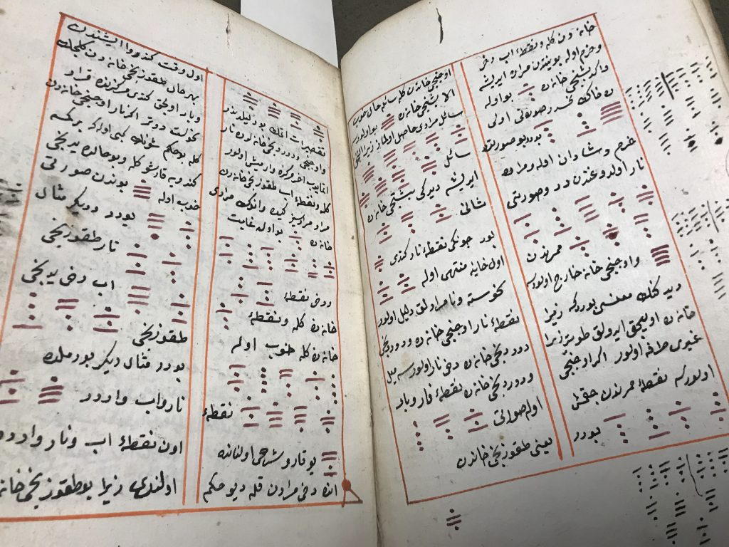 An open two page spread of an Arabic manuscript. The text is in two columns with red boxes surrounding it.
